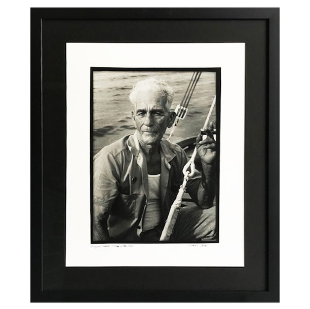 a framed photo of an old man on a boat that inspired Ernest Hemingway