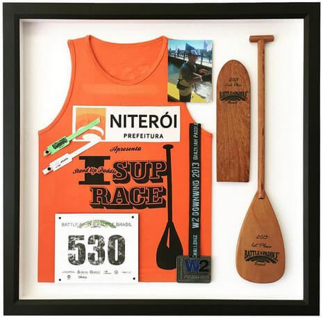 A jersey frame featuring an orange event jersey and other memorabilia.