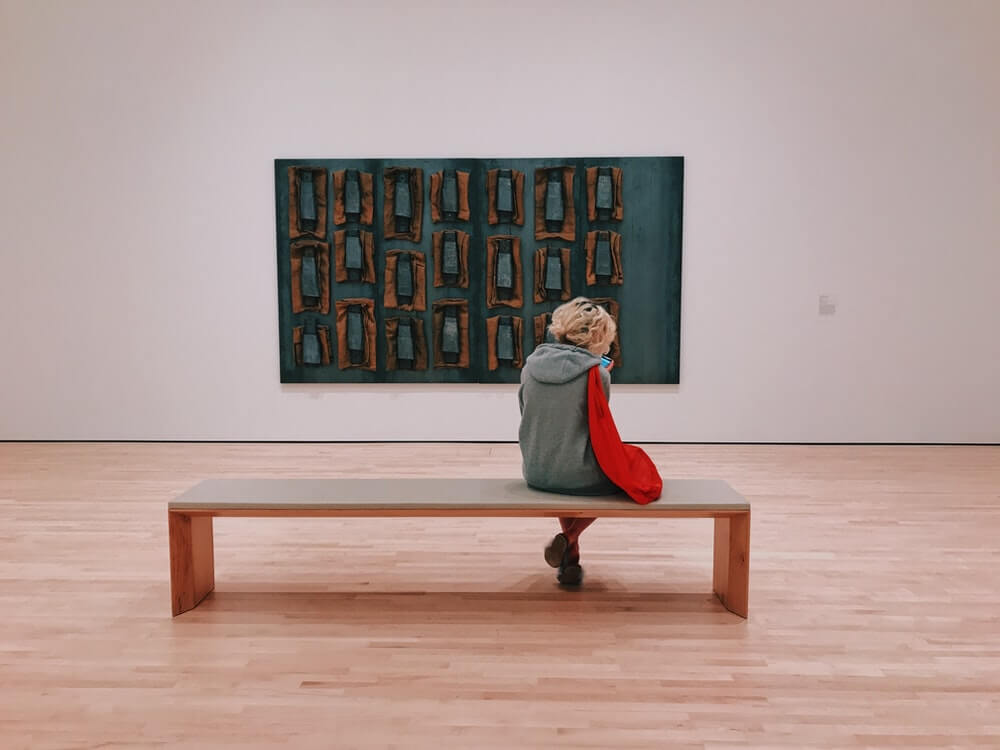 person sitting on a bench in a museum
