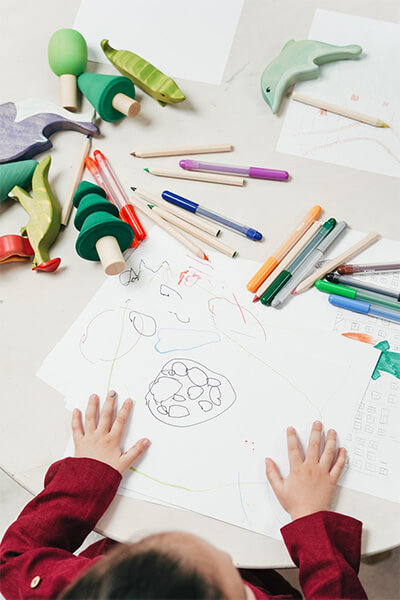 A young child uses markers and pens to create a drawing on a sheet of paper.