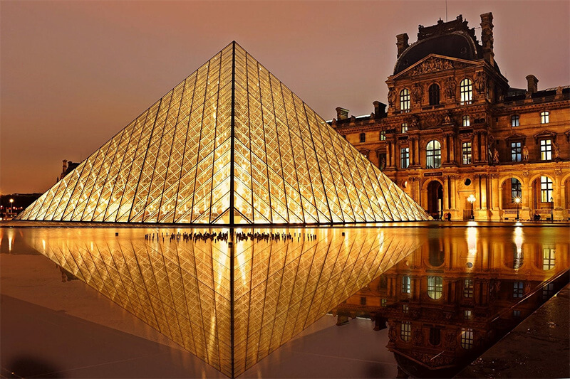 The illuminated Louvre Pyramid as seen in the evening.