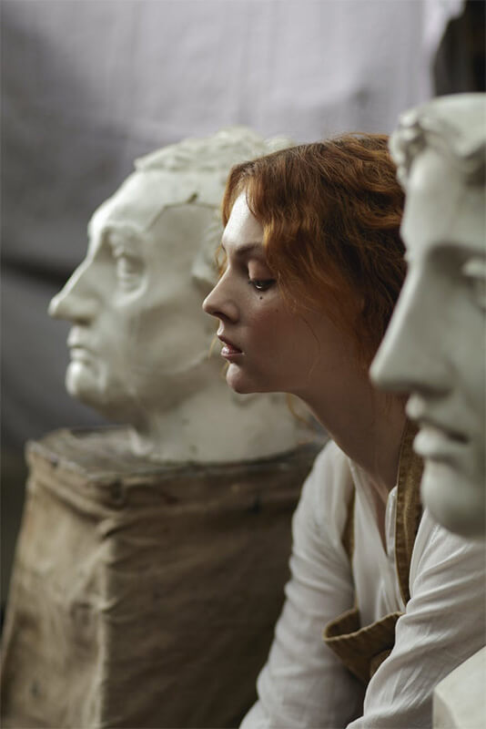 A woman sits in between two large busts while visiting a museum.