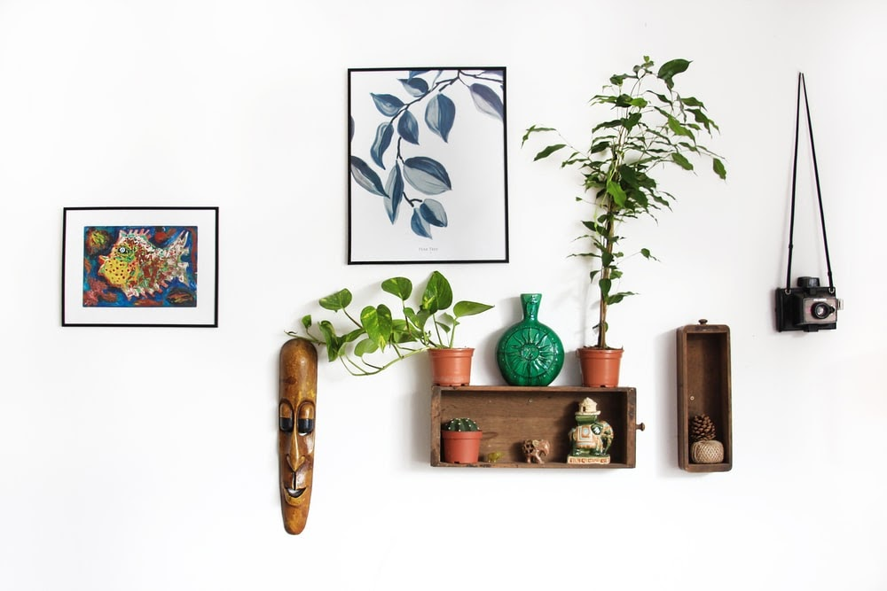 a wall decorated with canvas and shadow box framed art